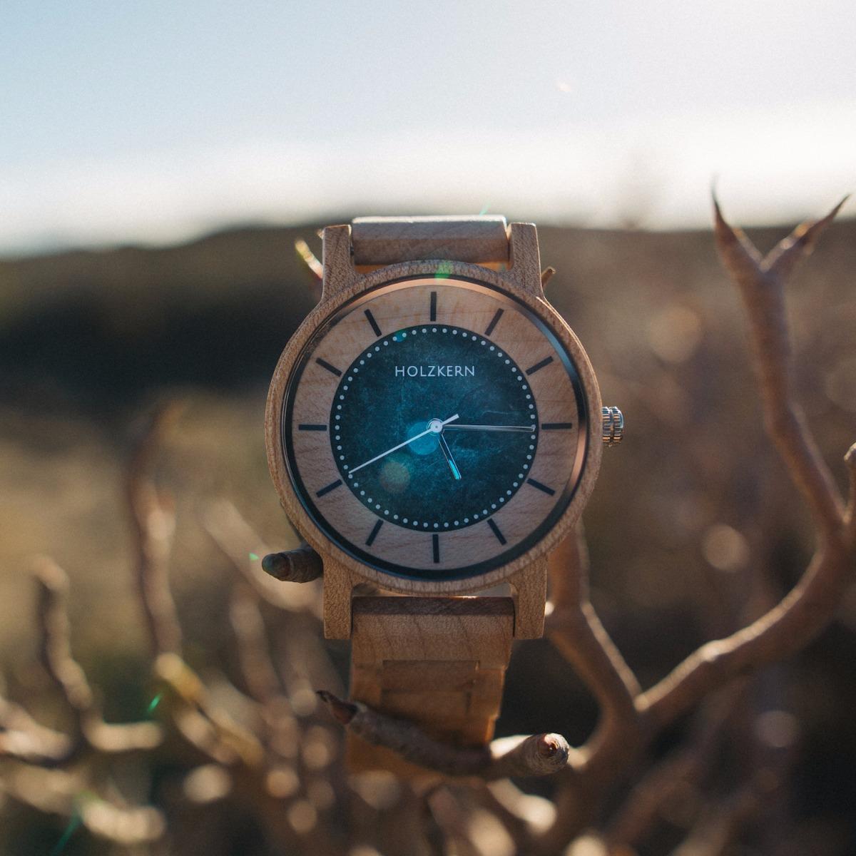 Die Holzuhr Alexander von Holzkern ist im Fokus, während man im Hintergrund hügelige Landschaften ausmachen kann
