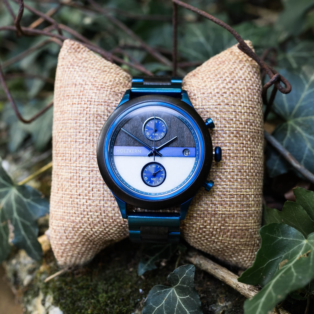 The wooden watch Bixby lies on a jewelry cushion in the forest