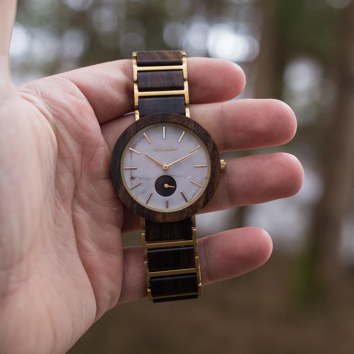 Holzkern Holzuhr Country sticht durch Ziffernblatt aus weißem Marmor und farbintensives Leadwood aus der Handinnenfläche des Trägers hervor