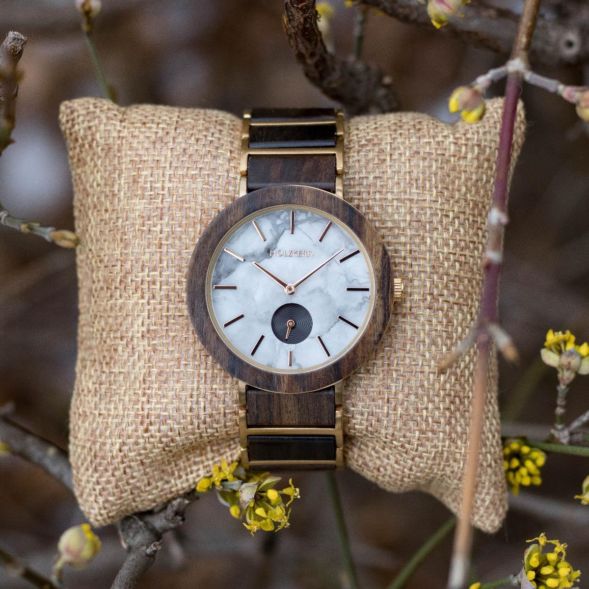 Holzkern Holzuhr aus Leadwood, weißem Marmor und goldenen Edelstahlakzenten auf einem Uhrenpolster umgeben von Geäst