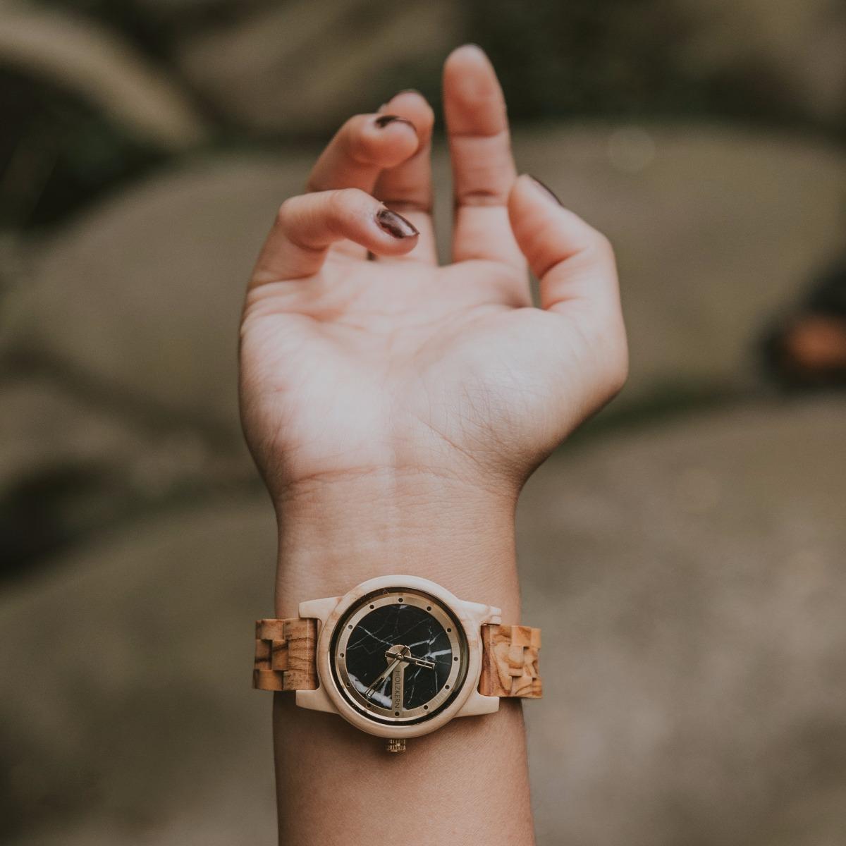 Im Bild sieht man den Arm einer Dame, die die Holzuhr Drei Zinnen von Holzkern trägt