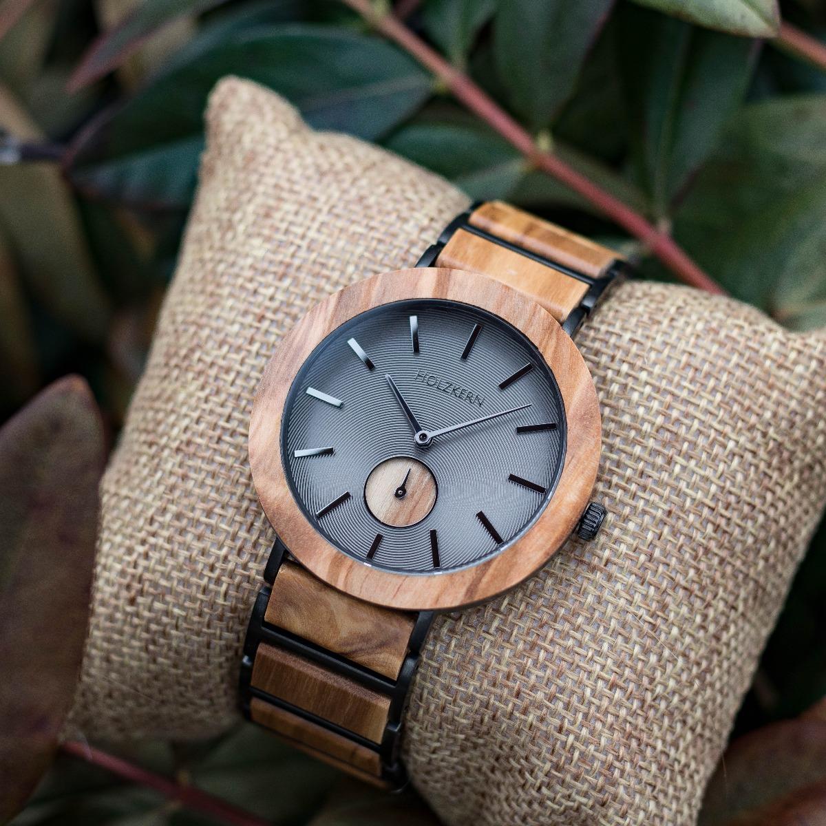 Holzuhr Gobi des Herstellers Holzkern auf einem Uhrenpolster umgeben von Blättern