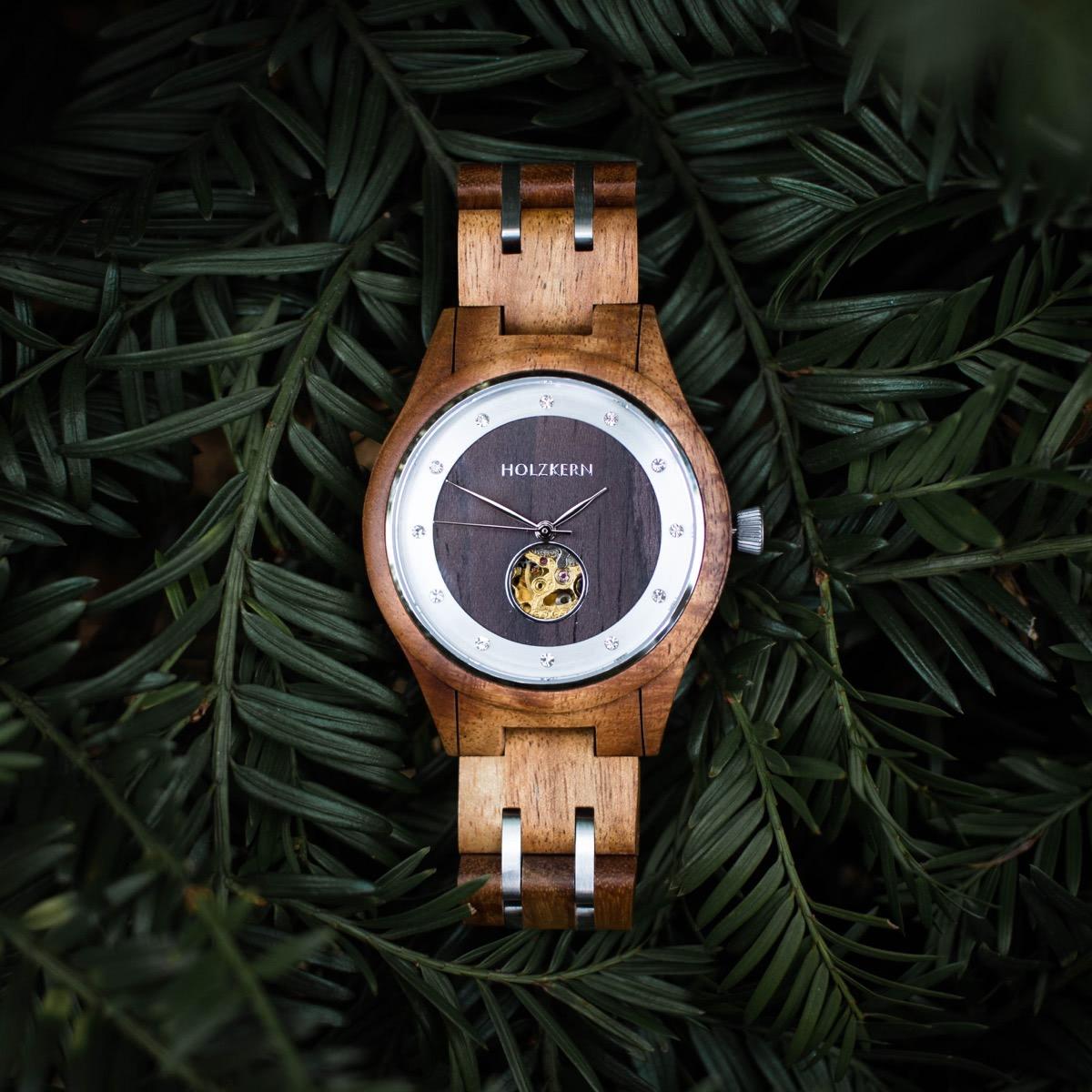 Holzkern Automatik-Holzuhr für Damen namens Gretel aus Walnuss und Leadwood auf grünen Tannenzweigen