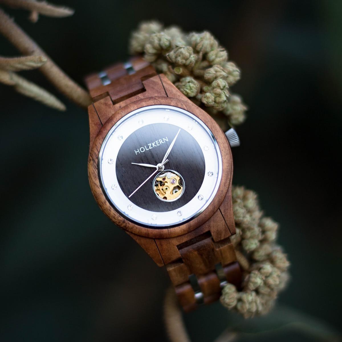 Damen-Holzuhr von Holzkern namens Gretel aus Walnuss und Leadwood mit mechanischem Uhrwerk mit Blüten im Hintergrund