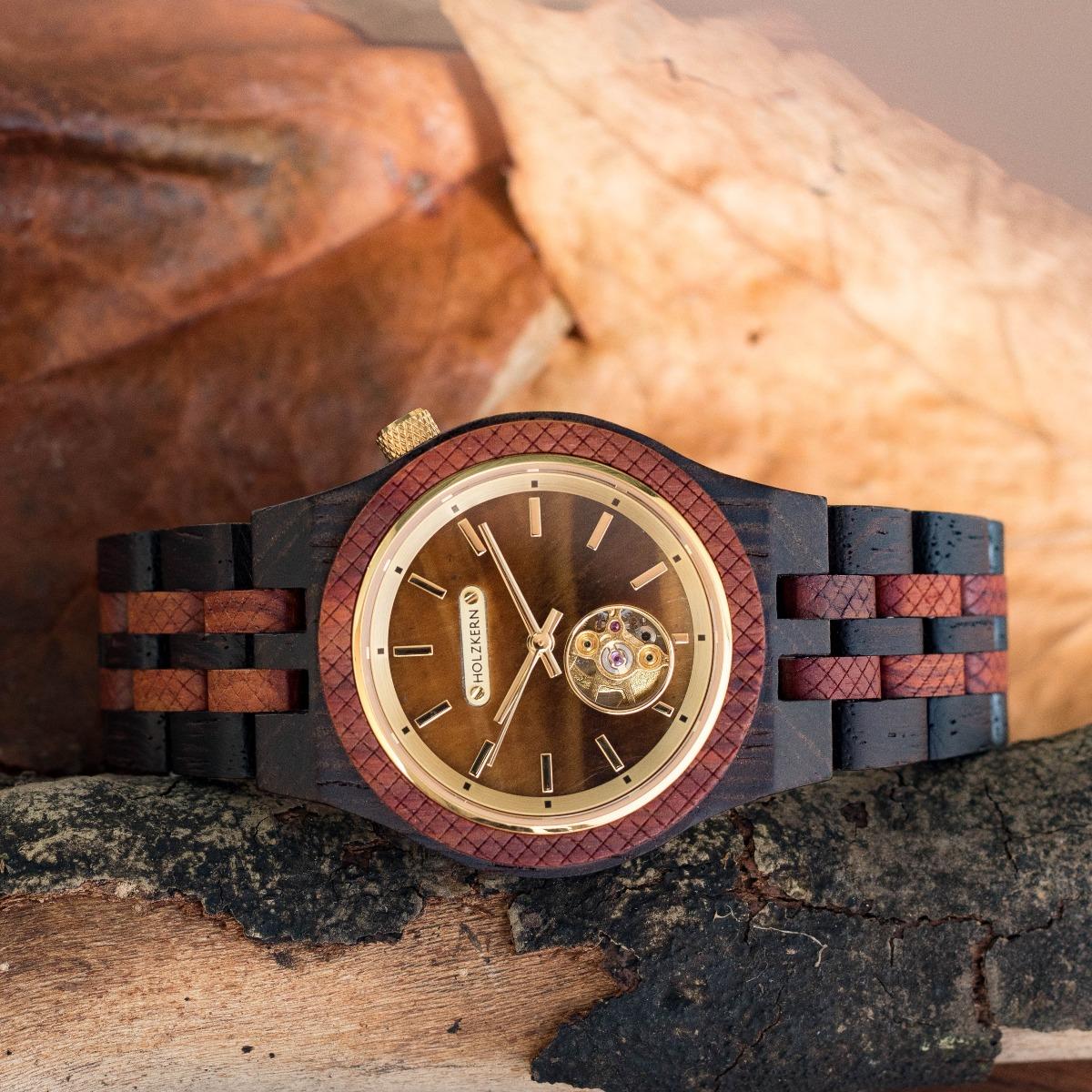 Heraklit ist eine Holzuhr von Holzkern, die sich durch ein Ziffernblatt aus echtem Tigerauge von allen anderen Modellen unterscheidet, die Sie je gesehen haben