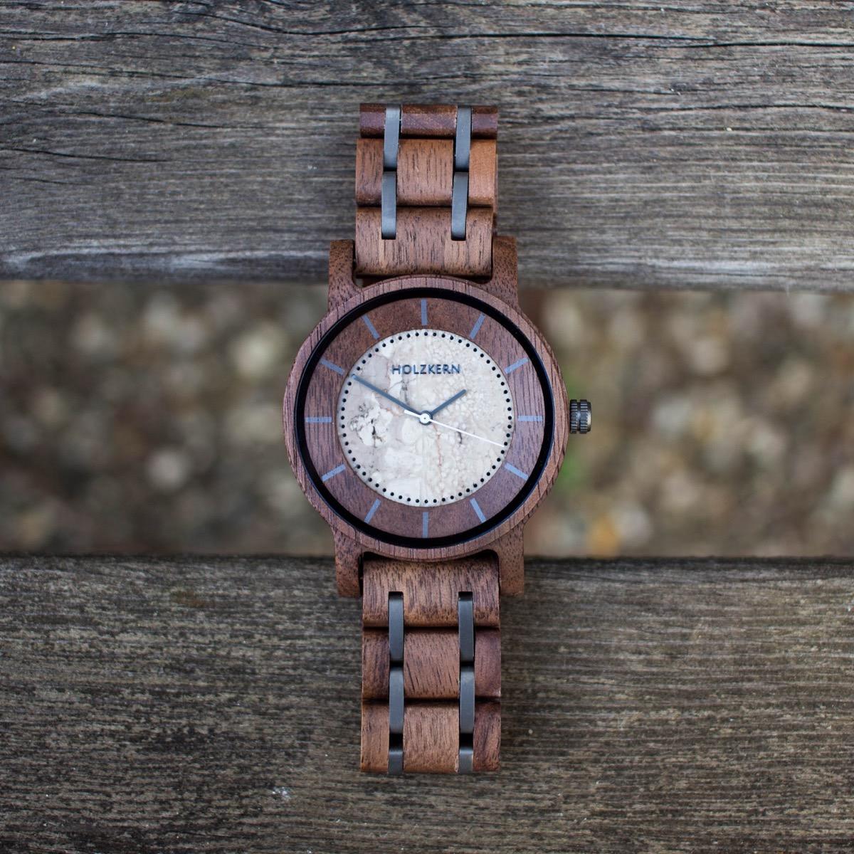 Die Holzuhr der Marke Holzkern mit dem Modellnamen James mit Walnuss-Gehäuse und Ziffernblatt aus echtem Jaspis liegt auf Holzbrettern