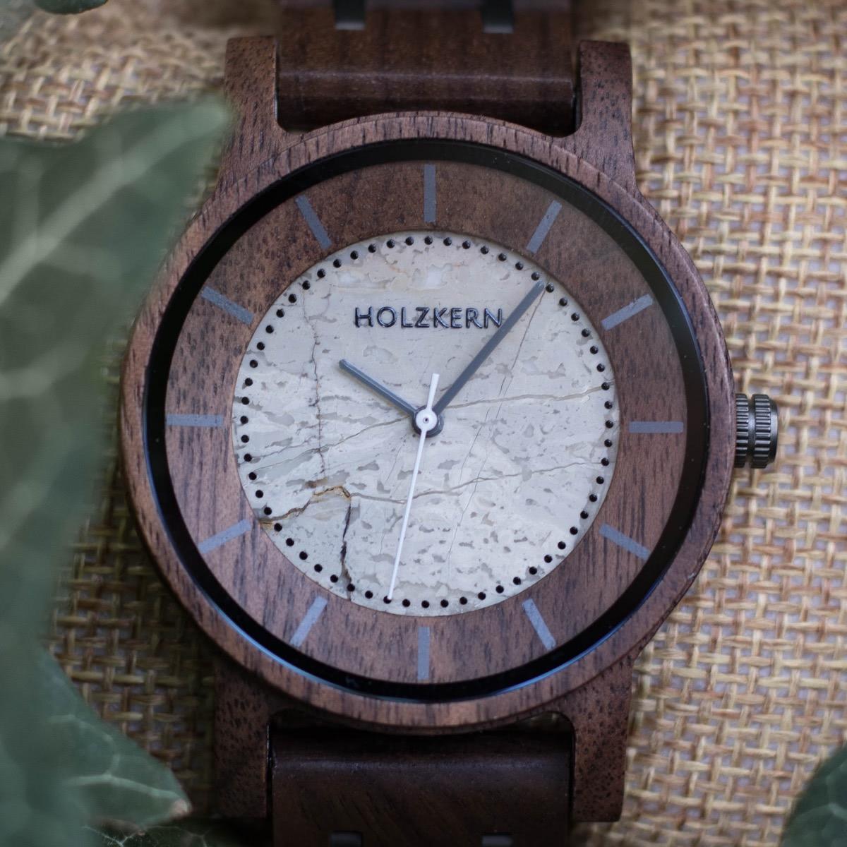 Nahansicht der Holzuhr James von Holzkern mit einem Ziffernblatt aus Jaspis und einem Gehäuse aus Walnuss auf einem Polster