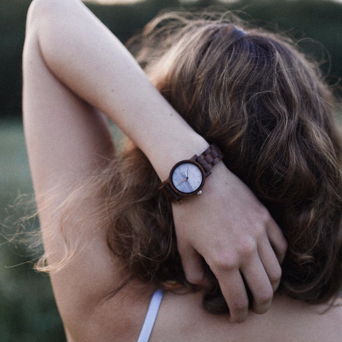 Wooden watch Air with a white marble dial on a woman's wrist