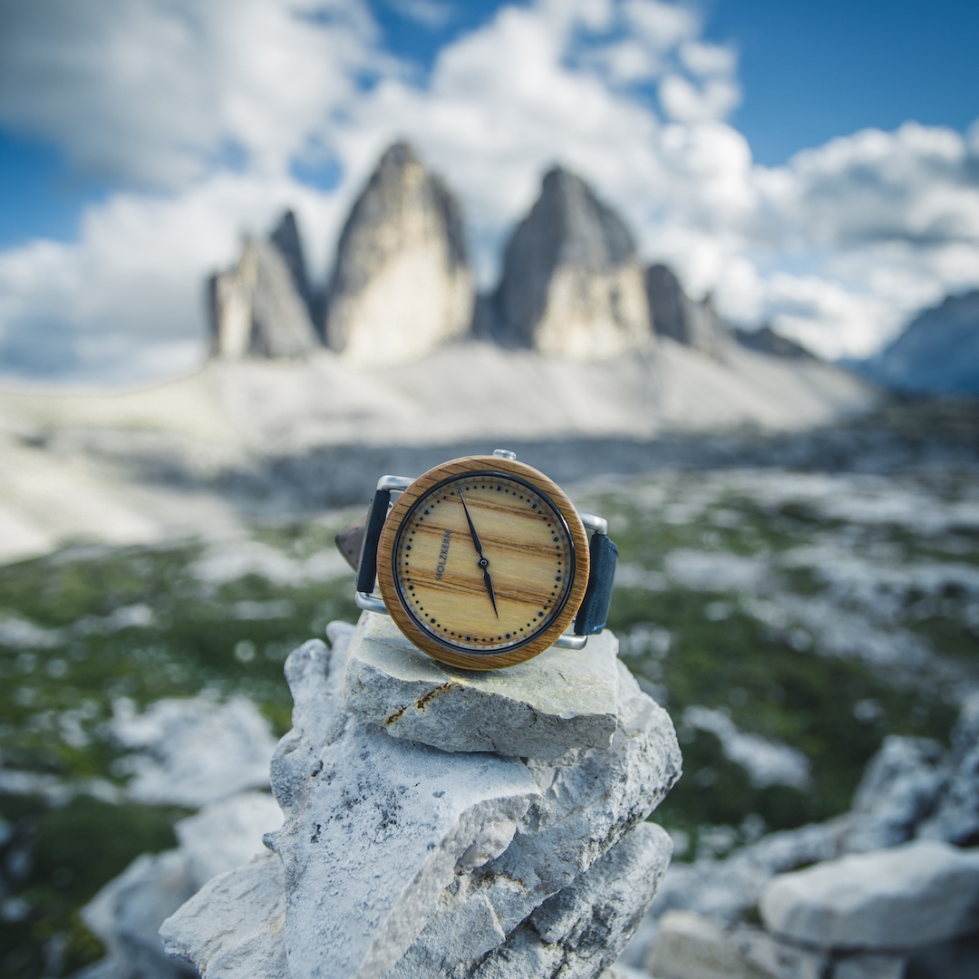 Die Holzuhr Merkur von Holzkern liegt auf einem Felsen umgeben von Berggipfeln und blauem Himmel