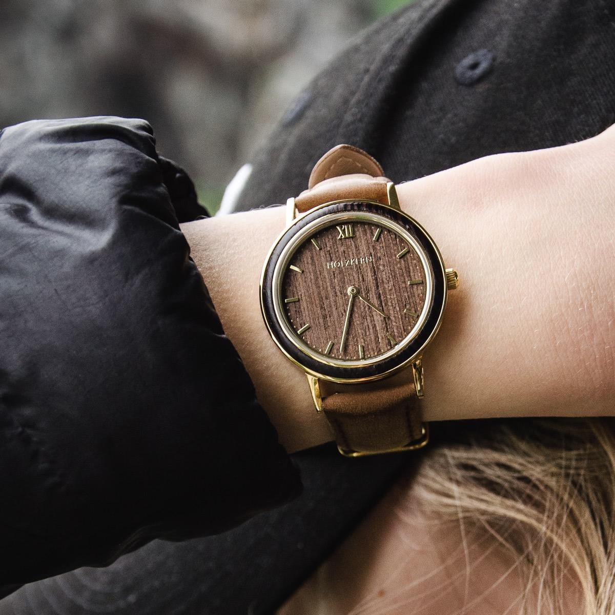 Holzkern Holzuhr Phoenix aus Wenge & goldenem Edelstahl ist ein besonders dünnes Modell, das im Bild am Handgelenk einer Dame zu sehen ist