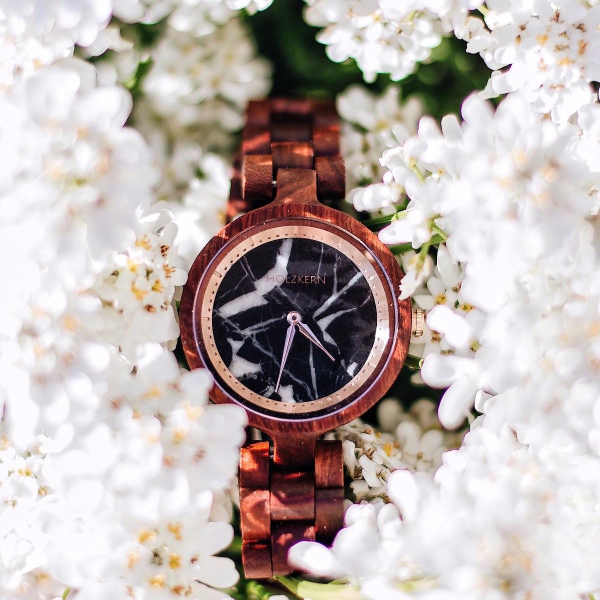 """Umgeben von weißen Blüten erkennt man die Holzuhr """"Schwarze Rose"""" von Holzkern mit einem Ziffernblatt aus echtem Marmor"""