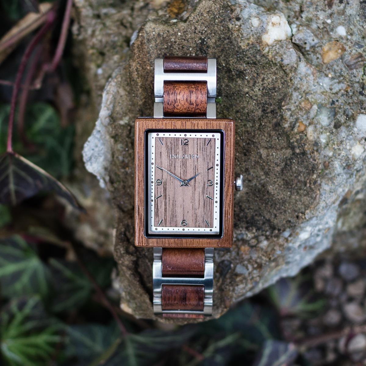 Unser Modell Spagna ist eine eckige Holzuhr aus Walnuss, die im Bild auf einem Felsen liegt